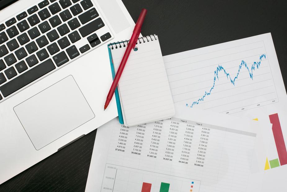 Laptop, charts, graphs, pens